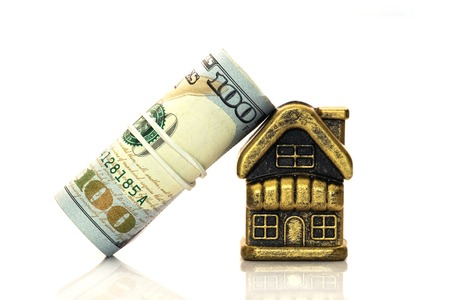 A roll of hundred dollar bills tied with a white rubber band leaned against the roof of a souvenir golden cottage. Concept mortgage, loan, pledge, financial pressure of the bank or the sale of real estate. Toy house on a white background. Copy space.