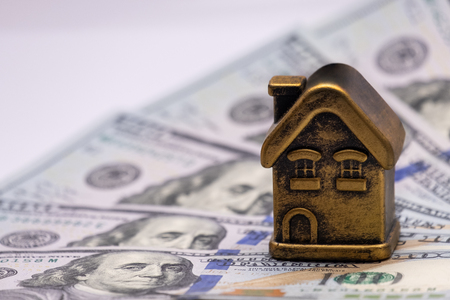 Private building or cottage on the background of paper money banknotes. Concept mortgage, loan, pledge, financial investments in real estate. Golden house and US dollars. Stock Photo - 117412372