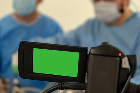 Video recording and live broadcast of the work of two surgeons. Green screen camcorder chromakey. Copy space. Operating room surgical hospital.