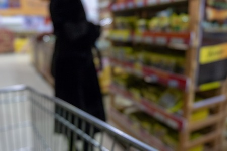 Blurred. Woman in black clothes near the shelves in the supermarket. Rows of products in the mall. View from the eyes of a visually impaired buyer. Stock Photo