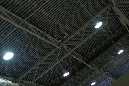 Metal roof hangar. Ceiling storage area with bright lamps. Abstract background.