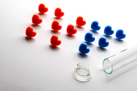 Failed in vitro fertilization. Broken test tube with a split neck. The letters composed of red and blue hearts on a white background. IVF. Copy space.