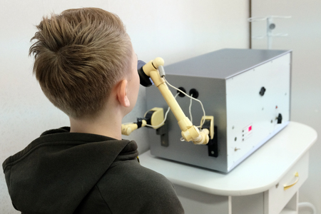An ultra high frequency medical device warms up the boys nose. A teenager in a jacket with a hood on a physiotherapy procedure UHF in a hospital. Stock Photo