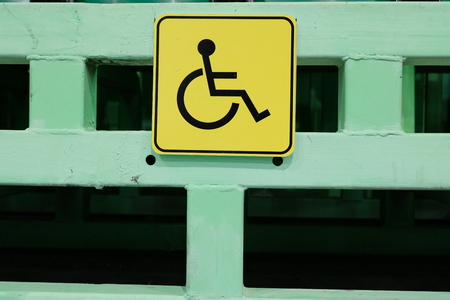 Protection and assistance for people with disabilities. Yellow sign is a place for disabled people. Social sphere of life. Stock Photo