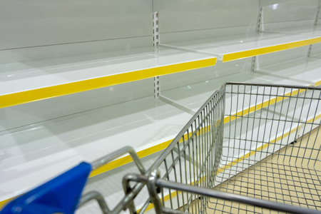 Empty shelves and part of a grocery cart in a supermarket. Shopping concept. Copy space. Stock Photo