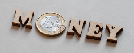 Word MONEY from wooden letters and one euro on a gray background. Symbolic inscription of the design of advertising on the Internet or web banner. Monetary concept of financial investments or transactions.