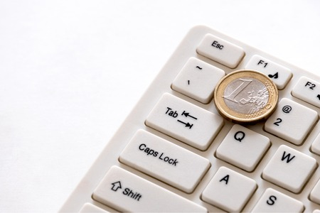 Euro coin lies on the key with the number one on a computer keyboard. How much do programmers in Europe earn. Concept of finance and technology. How to make money online and income freelancer. White background.