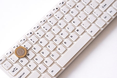 Two argentinian peso coin on white keyboard background. Concept of finance and computer technology. How to make money online. Small payment to programmers or income freelancer. White background. Stock Photo
