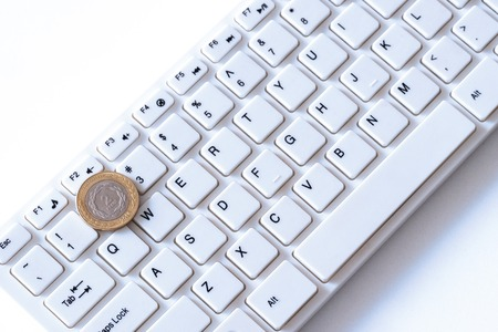 How much do programmers in Argentina earn or a peso coin lies on the key with the number two on a computer keyboard. Concept of finance and technology. How to make money online and income freelancer. White background.