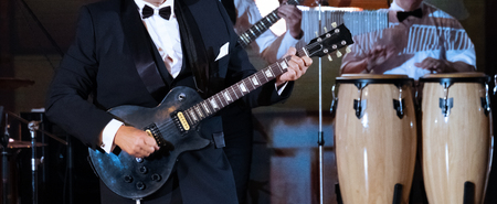 Jazz band performance. An abstract man in a strict suit plays the guitar on the scene in the foreground. Close-up. Drums in the background. Concept for the design of a musical theme.