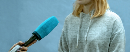 The girl the blonde in a sports light sweater gives interviews. Abstract image of a teenager. Female correspondent hand is holding a blue microphone. Copy space. The concept of news reporting.