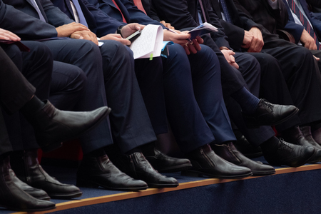 Mens legs in trousers and black shoes. Officials are sitting in the meeting room. Documents and phones in hand.