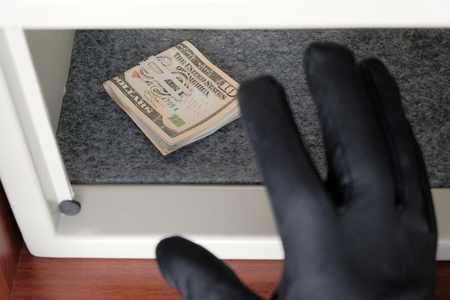 A black gloved hand reaches for the money. US dollar bills in a safe deposit box. The concept of saving money in a hotel or bank, crime and theft. Shallow depth of field. Selective focus.