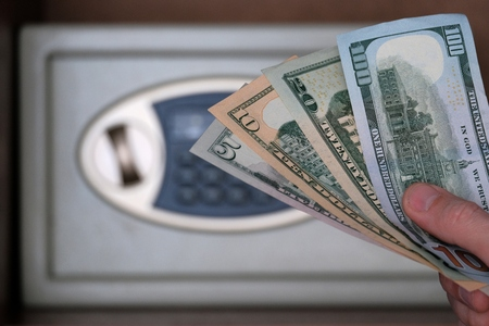Banknotes of US dollars in a male hand against the background of a safe box. The concept of saving money in a hotel or bank, storing banknotes in a safe with a combination lock. Shallow depth of field. Stockfoto