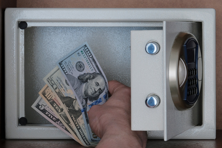 Close-up of a mans hand putting American dollars in a safe Deposit box. Storage of money, stocks and jewelry in a Bank Cabinet. Banknotes of 5, 10, 20, 100 US dollar.