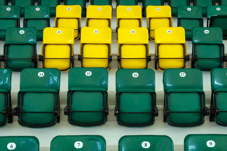 Yellow and green plastic seats in the stands of the sports complex. Seats for spectators of a football match indoors. Auditorium for sports fans.