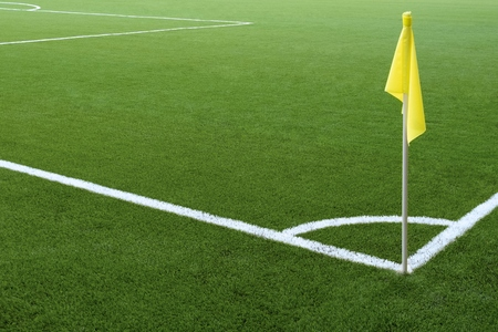White markings on green grass and yellow flag. Corner of a football field. No people and players. Sports concept. Reklamní fotografie