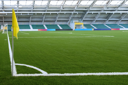Corner of a soccer field in an indoor stadium. Yellow flag, white marking on green grass. Spectator stands in the background. Copy space, mock-up for billboards.