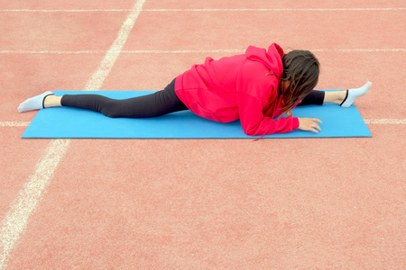 A young girl sitting on a longitudinal twine on a fitness carpet. Women's stretching classes in nature. Concept of healthy life and natural balance between body and mental development. Pink background. Standard-Bild