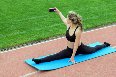 The girl sits on the splits. Young beautiful woman with a mobile phone in her hand is doing selfie during gymnastic exercises. Female stretching legs on a rug in the park.