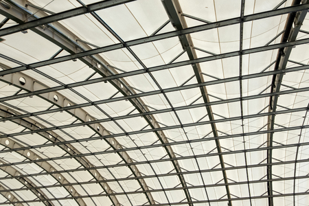 Part of the semicircular roof of a modern building. Texture background. The ceiling in the hangar, shopping, sports or industrial building.
