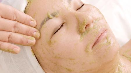 Das Mädchen im Schönheitssalon nimmt eine Gesichtsbehandlung. Nahaufnahme einer Frau mit einer Maske aus Grünalgen Spirulina im Gesicht. Verjüngung, Entspannung und Heilung der Haut.