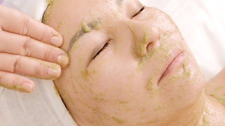 The girl in the beauty salon takes a facial. Close-up of a woman with a mask of green algae spirulina on her face. Rejuvenation, relaxation and healing of the skin.