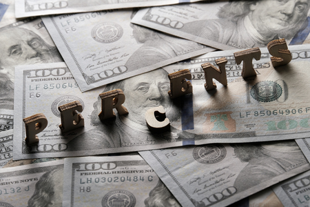 The concept of financial transactions and bank loans. The word PERCENTS is lined with wooden letters on the background of hundred-dollar bills.