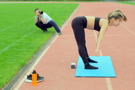 The photographer takes a picture of a girl who does yoga. Stretching classes at the stadium in the fresh air. A report for a sports magazine.