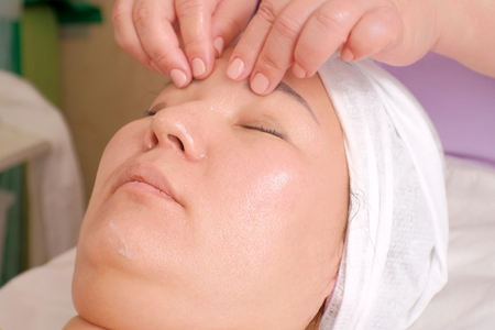 Facial massage against wrinkles for women in the beauty salon. Beautician kneads the girls face. Lifting effect. Beauty. Healthy facial skin and body