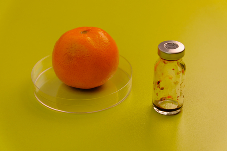 Ripe tangerine and a medicine bottle on a green table. Laboratory work on fruit. Citrus tests for the presence of GMOs.