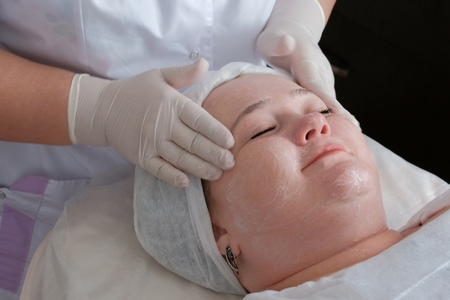 Therapeutic and cosmetological facial massage of a fat woman in the health and beauty salon.The hands of a professional beautician in white medical gloves smooth the skin face of a smiling girl.