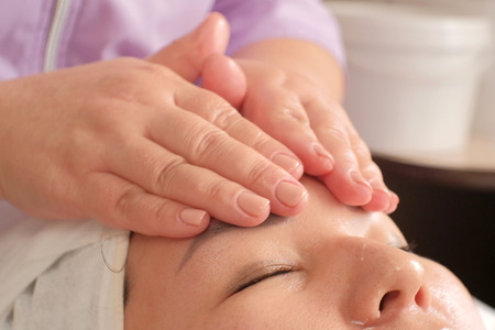 Closeup of massage on the female forehead. Smoothing wrinkles on the womans face. Face and body care in the beauty salon.