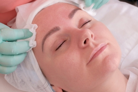 Cleansing and moisturizing the skin. Beautician wipes wet wipes a woman's face. Beauty and health in the beauty parlor.