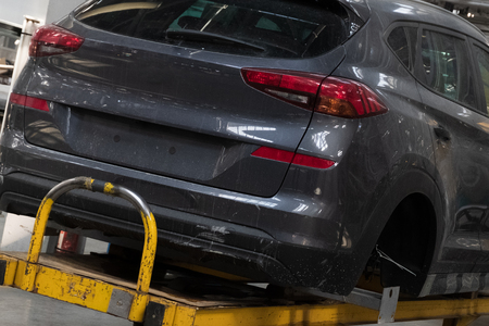 Part of a dark gray car body without wheels on a lift. Assembling cars at the factory. Industrial vehicle production line.