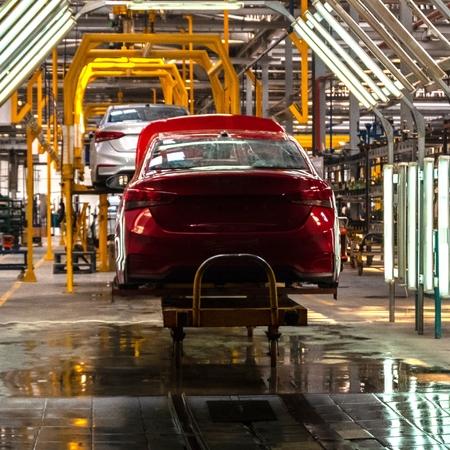 Die Karosserie des roten Autos am Fließband. Werksfahrzeuge oder Autowerkstatt oder Autotuning-Studio. Quadratischer Rahmen