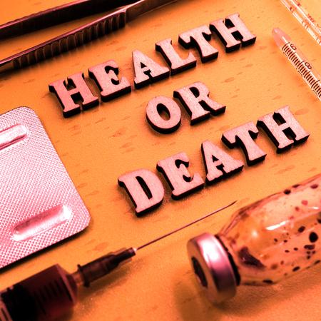 Health or death concept. The inscription of wooden letters. Toning in vintage style. Potent drug, syringe, bottle of medication. Square frame for instagram. Medical theme.