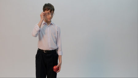 A student dressed in a white shirt and black pants is holding an apple in one hand, while the other straightens his glasses. Light background. Back to school. Copy space.