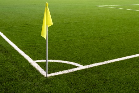 Yellow flag on the corner of a football field. Place for a corner kick on a soccer ball. White line marking sports field for football players.