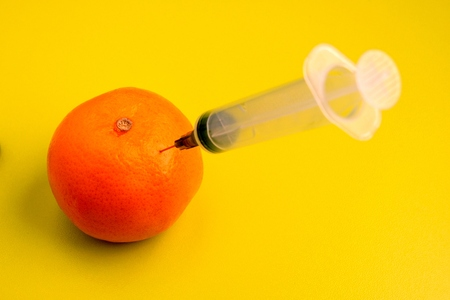 Ripe tangerine with a syringe on the table in the laboratory. Genetically modified fruits and vegetables. Acid yellow-green background. Stok Fotoğraf