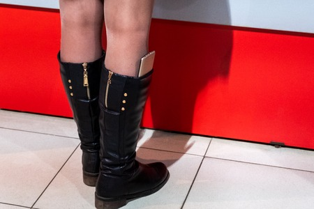 Mobile phone sticks out of the womens boot. Womens legs at the bar on a red background.