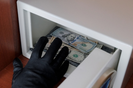 A man in a black glove steals banknotes from a metal safe with a combination lock. Criminal concept of theft of financial assets in an office or hotel. Breaking into a safety Deposit box.