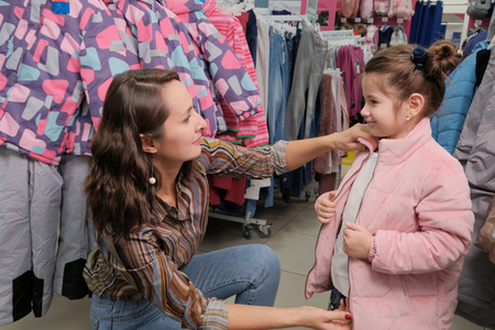 Happy young mother and daughter shopping. Girl trying on a jacket for the winter in a childrens clothing store.
