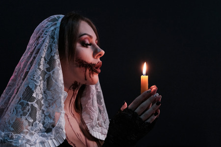 A beautiful girl dressed as a terrible nun holds a lit candle. Woman portrait with halloween makeup. Black background. Concept for a horror poster or an invitation to a party of fear.