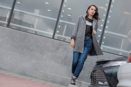A beautiful girl walks through the city past a parking lot next to a shopping center shop window. Brunette in a coat and jeans walks on the side of the road. Woman model posing for a fashionable photo on the street. The weather is autumn or spring.