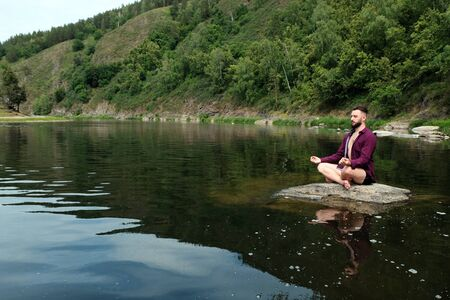 A young man of like Caucasian appearance in a plaid shirt is sitting on a stone in a river or lake. The concept of yoga, relaxation, unity with nature, travel and lifestyle. Copy space.