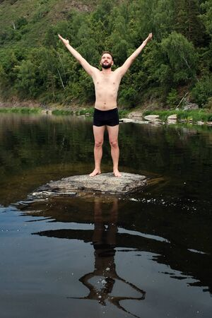 Brutal Caucasian guy with a beard in swimming trunks stands on a stone in the water among the mountains and raised his hands to the sky The concept of human unity with nature, travel and lifestyle.