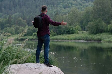 A young man traveler with a backpack in jeans and a shirt stands on a stone on the bank of a mountain river and looks ahead. The concept of human unity with nature, travel and lifestyle. Copy space.