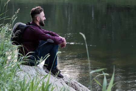 Joyful stylish guy with a beard. Traveler with a backpack in jeans and shirt is sitting on a stone by the river and looking ahead. The concept of human unity with nature, travel and lifestyle.