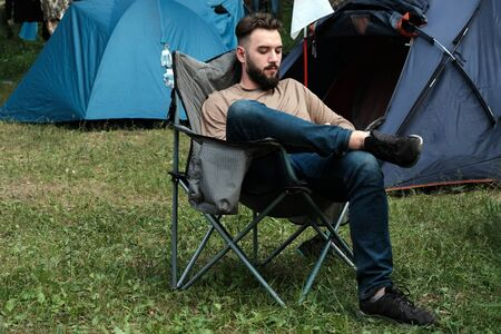 A guy with a beard in jeans and a t-shirt is sitting on a folding chair on a green meadow in the forest near the tents. The concept of man's leisure in nature, travel and lifestyle, mountaineering.